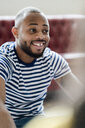 Portrait of smiling young man wearing striped t-shirt - GIOF05134