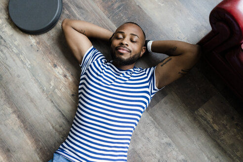 Smiling young man lying on wooden floor with closed eyes - GIOF05140