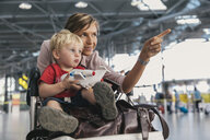 Germany, Cologne, portrait of mother and little son with baggage cart at airport terminal - MFF04714