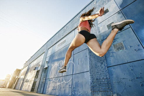 Low angle view of female athlete running along sidewalk past blue building covered in graffiti. - MINF09813