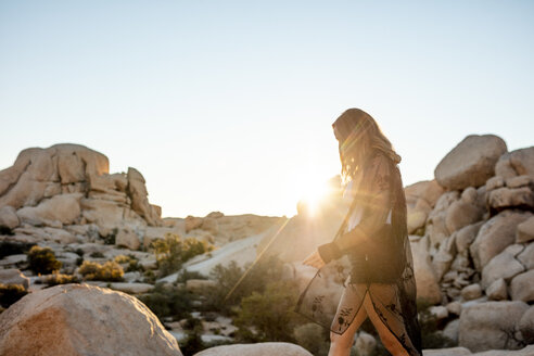 USA, California, Los Angeles, woman walking on rocks in backlight in Joshua Tree National Park - DAWF00846