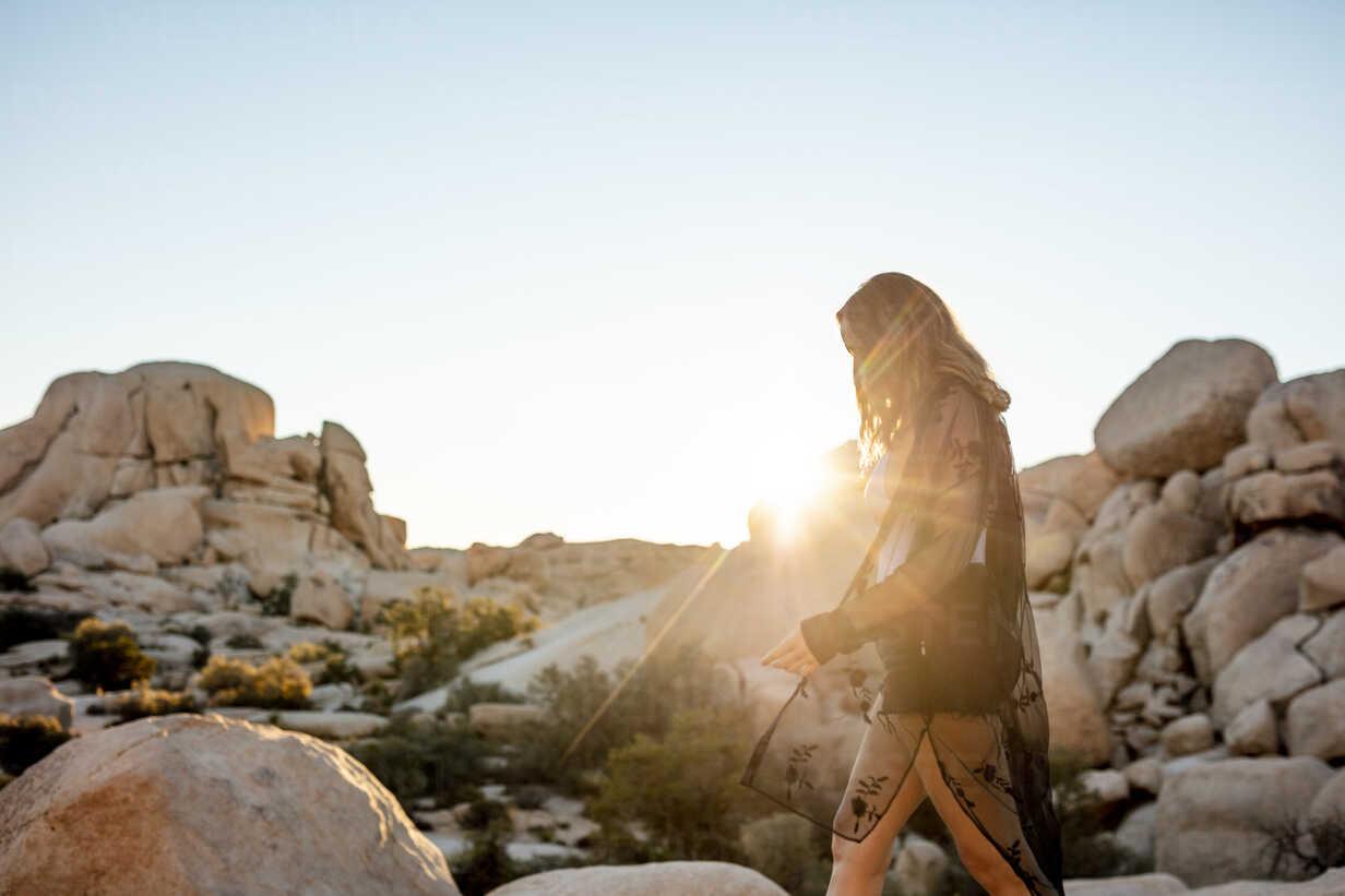 USA, California, Los Angeles, woman walking on rocks in backlight in Joshua Tree National Park - DAWF00846 - Daniel Waschnig Photography/Westend61
