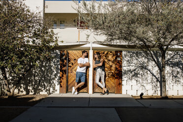 USA, California, Palm Springs, smiling couple standing at house entrance - DAWF00870