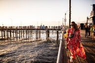 USA, California, Santa Monica, smiling woman walking on the pier - DAWF00873