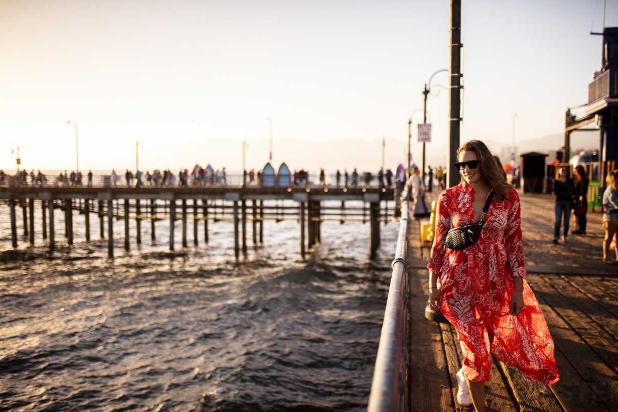 USA, California, Santa Monica, smiling woman walking on the pier - DAWF00873 - Daniel Waschnig Photography/Westend61