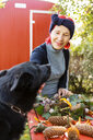 Portrait of smiling senior woman with red dyed hair tinkering autumnal decoration while stroking her dog - OJF00294