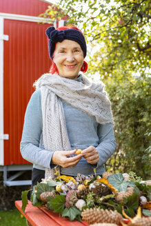 Portrait of smiling senior woman with red dyed hair tinkering autumnal decoration in the garden - OJF00300