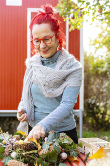Portrait of smiling senior woman with red dyed hair tinkering autumnal decoration in the garden - OJF00303