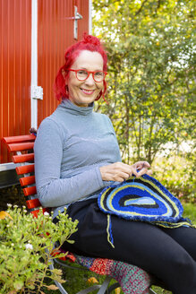 Portrait of smiling senior woman with red dyed hair sitting in front of red trailer in the garden crocheting - OJF00306