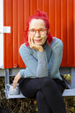 Portrait of content senior woman with red dyed hair sitting in front of red trailer in the garden - OJF00309