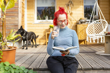 Portrait of smiling senior woman with red dyed hair sitting on terrace in front of her house reading a book - OJF00312