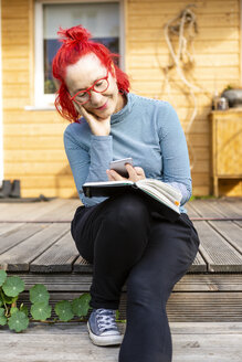 Portrait of smiling senior woman with red dyed hair sitting on terrace in front of her house using cell phone - OJF00315