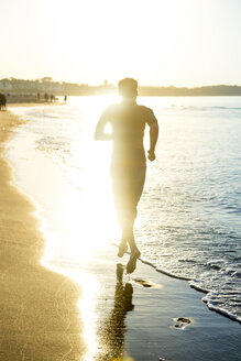 Man jogging at the beach at sunset - PUF01351