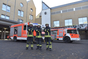 Portrait of three confident firefighters standing on yard in front of fire engine - LYF00843