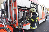 Firefighter standing at fire engine - LYF00849