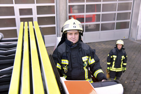 Portrait of two confident firefighters exercising at fire engine - LYF00852