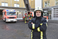Portrait of confident firefighter in front of fire engine with colleagues in background - LYF00855