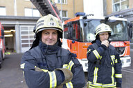 Portrait of two confident firefighters in front of fire engine - LYF00861