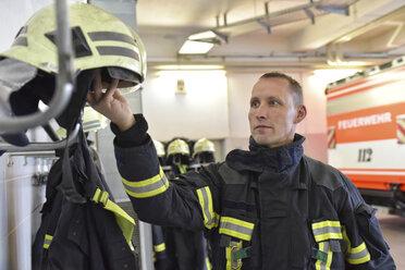 Firefighter taking helmet from rack in fire station - LYF00864