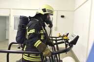 Firefighter with respirator and air tank exercising on treadmill - LYF00867