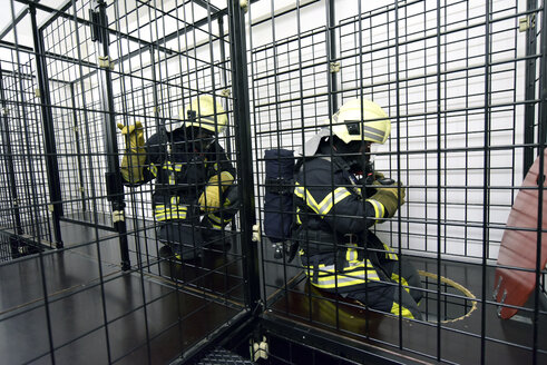 Two firefighters with respirator and air tank exercising - LYF00870