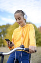 Portrait of smiling girl with headphones and bicycle looking at smartphone - BFRF01949
