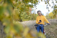 Smiling girl with headphones sitting on bicycle looking at smartphone - BFRF01952