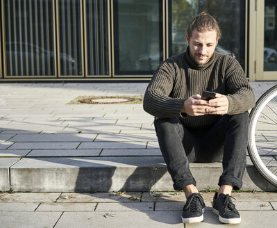 Portrait of bearded young man sitting on curb next to bicycle using cell phone - FMKF05338