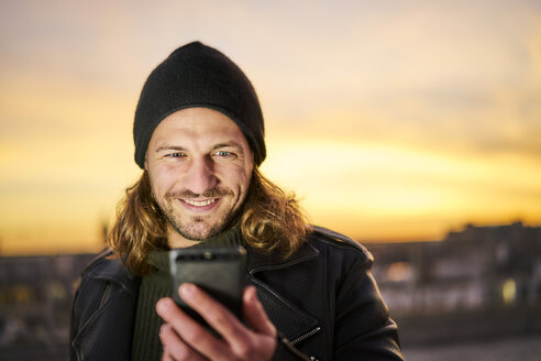 Portrait of bearded young man wearing wooly hat looking at mobile phone by sunset - FMKF05350