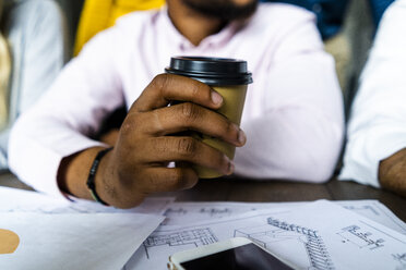 Close-up of businessman holding disposable coffee cup during a meeting in office - GIOF05185