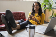Young businesswoman sitting with feet on desk holding cell phone - GIOF05218