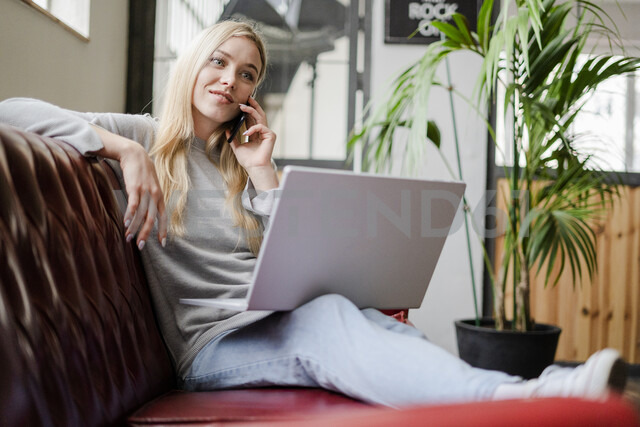Smiling young woman sitting on couch with laptop talking on cell phone - GIOF05224