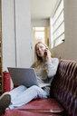 Smiling young woman sitting on couch with laptop talking on cell phone - GIOF05227