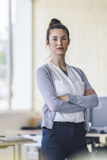 Portrait of a beautiful young woman, standing in office, with arms crossed - RIBF00780