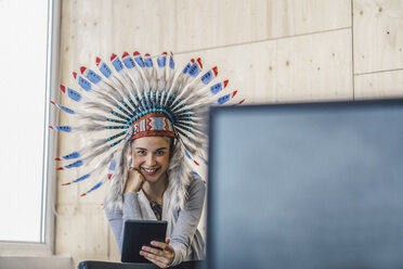 Young woman wearing Indian headdress, standing in office, using digital tablet - RIBF00792
