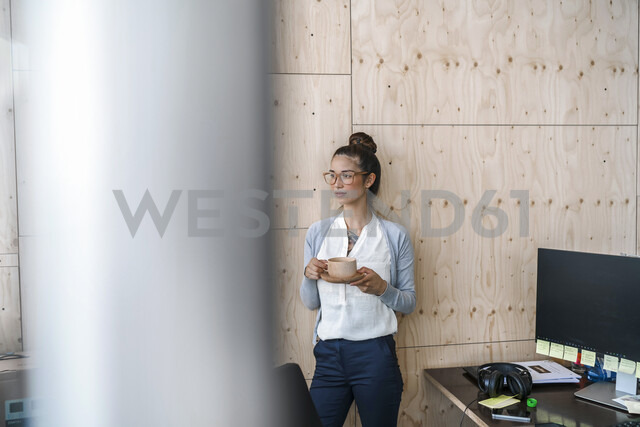 Young woman working in creative office, taking a break, drinking coffee from wooden cup - RIBF00795 - Richárd Bellevue/Westend61