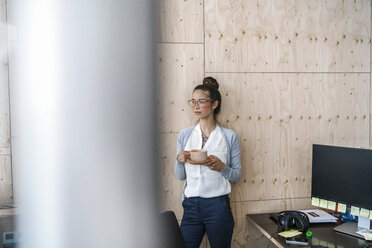 Young woman working in creative office, taking a break, drinking coffee from wooden cup - RIBF00795