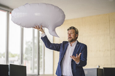 Businessman standing in office, holding inflatable speech bubble - RIBF00798