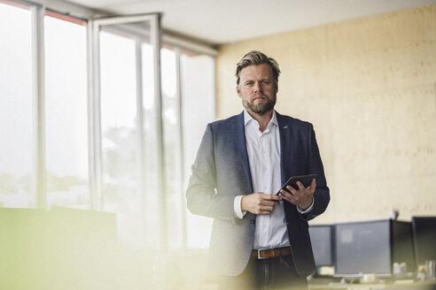 Businessman standing in office, using digital talet - RIBF00801
