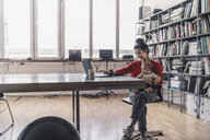 Working mother with baby on her lap, sitting in office, using laptop - RIBF00822