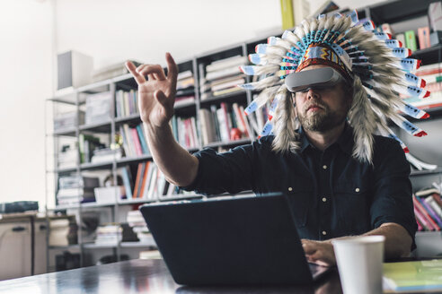 Man wearing Indian headdress and VR glasses in office, using laptop - RIBF00828