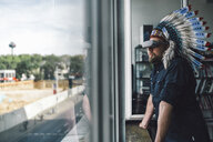 Man wearing Indian headdress and VR glasses in office, looking out of window - RIBF00831