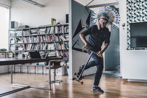 Man wearing Indian headdress and VR glasses in office, using kick scooter - RIBF00834