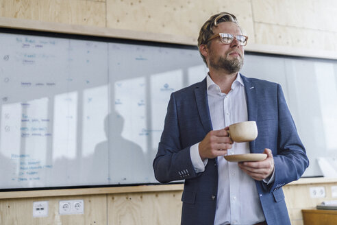Businessman standing in his office in front of whiteboard, drinking coffee from a wooden cup - RIBF00846