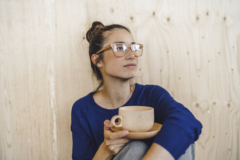 Young woman taking a break in office, drinking coffee from a wooden cup - RIBF00852