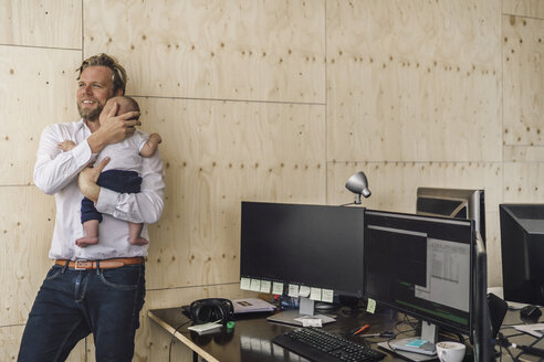 Working father standing in office, holding his son - RIBF00855