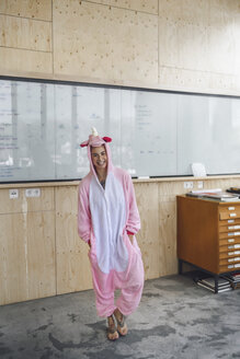 Woman wearing unicorn onesie, standing in front of whiteboard, laughing - RIBF00861