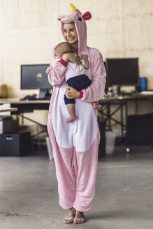 Young mother wearing unicorn onesie, standing in office, holding her son in her arms - RIBF00864