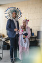 Man and woman, dressed as Indian and unicorn, standing in office, woman holding baby in her arms - RIBF00870