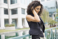 Thoughtful woman standing against railing outdoors - HEROF00045